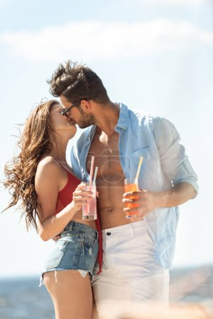 Photo for Happy couple kissing and holding alcohol cocktails - Royalty Free Image