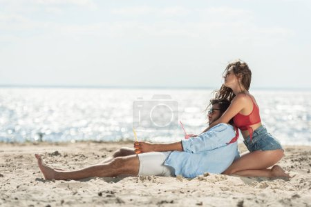 couple with beverages relaxing on beach near the sea