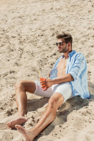 handsome bearded man in sunglasses sitting on sandy beach with glass of alcohol cocktail