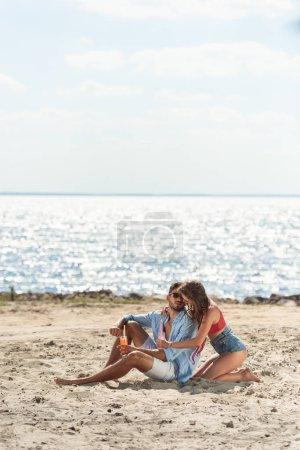 couple avec des cocktails assis sur la plage près de la mer