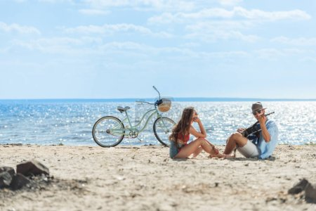 handsome man playing on guitar for his girlfriend and resting on beach with bike
