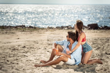 attractive couple with cocktails in glasses sitting on beach and looking at sea