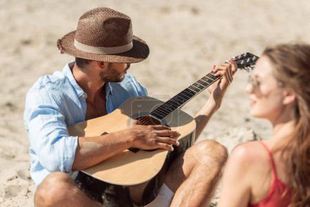 handsome man in hat playing on acoustic guitar for his girlfriend
