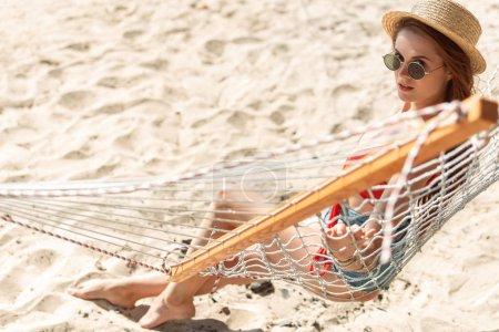 attractive girl in straw hat resting in hammock on sandy beach