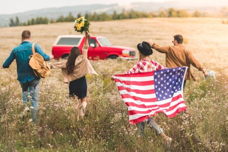 rear view of group of young american travellers with flag walking by flower field during car trip