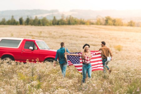 group of young friends with united states flag in flower field during car trip