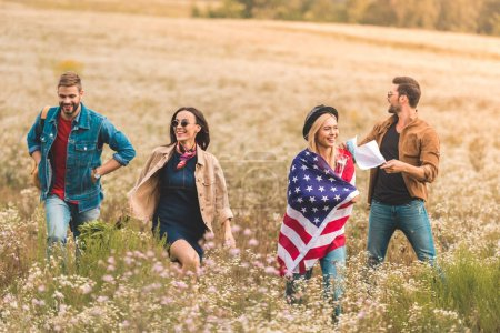group of young americans with flag walking by flower field