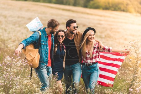 group of smiling young american travellers with flag walking by flower field