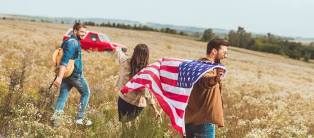 group of friends with united states flag in flower field during car trip