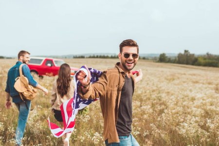 handsome young man with united states flag in flower field with friend during car trip