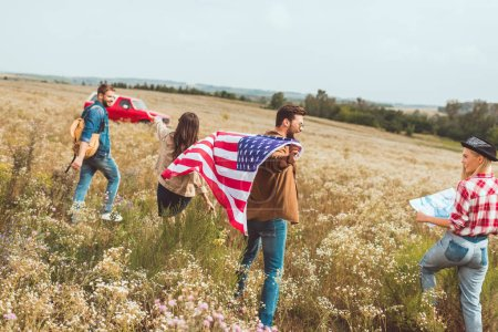 group of happy young american travellers with flag walking by flower field