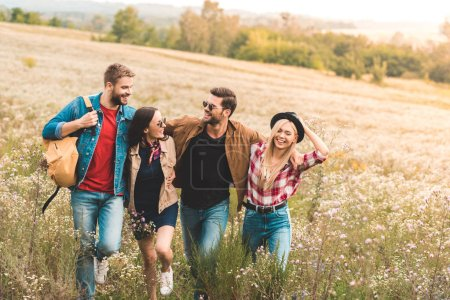 group of happy young friends embracing and walking by field together during trip