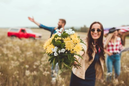young happy woman showing flower bouquet at camera with happy friends walking behind
