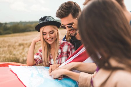 group of happy young friends planning car trip with map on engine hood