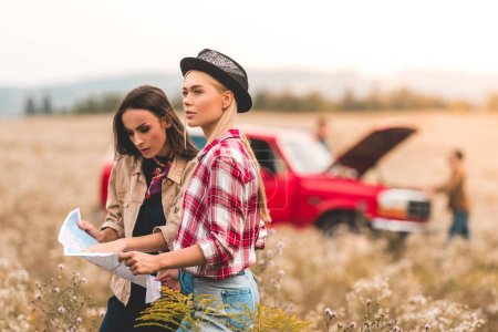 serious young girlfriends with map standing in field and trying to navigate