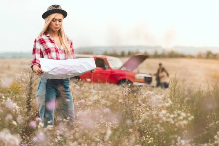young woman looking at map in flower field while her friends standing near broken car blurred on background