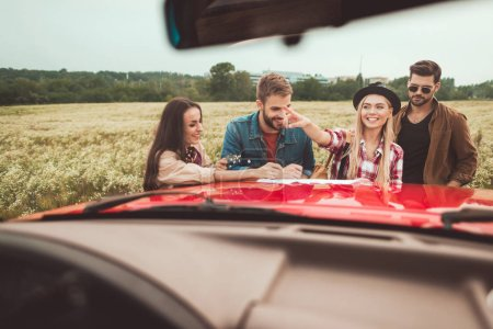 view from car at group of travellers planning trip in flower field