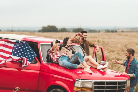 group of young american car travellers relaxing in flower field