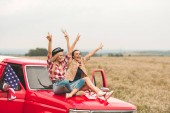 beautiful young girlfriends sitting on car hood with raised hands and showing peace signs