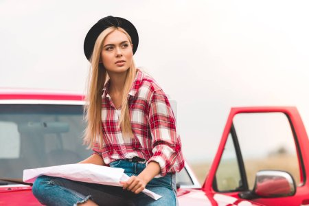 beautiful young woman sitting on car with map and looking away