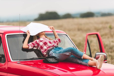 Photo for Young woman lying on hood of vintage red truck in field and covering face with map in field - Royalty Free Image