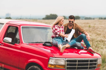 travelling young couple sitting on car engine hood and navigating with map