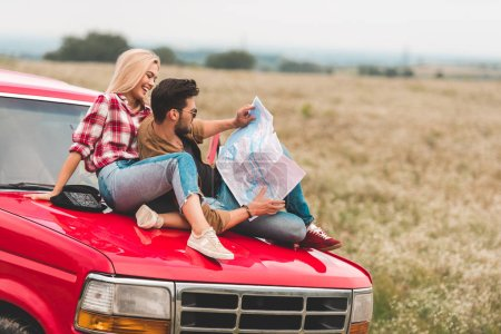 beautiful young couple sitting on car engine hood and navigating with map