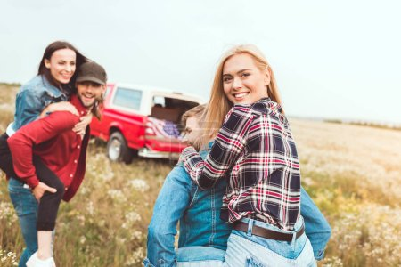 young women piggybacking on boyfriends and looking at camera in field
