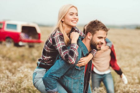 attractive young woman piggybacking on boyfriends back