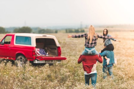 young women riding on boyfriends shoulders in field during car trip
