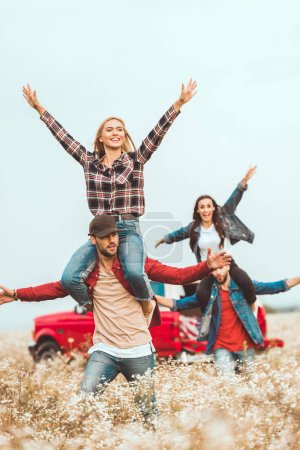 young women riding on boyfriends shoulders and raising hands in field