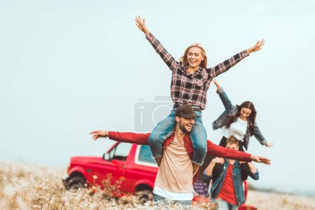 young women riding on boyfriends shoulders and raising hands in field during car trip