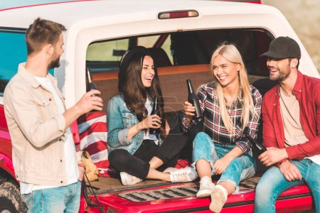 group of young people drinking beer and chatting while sitting in car trunk on nature