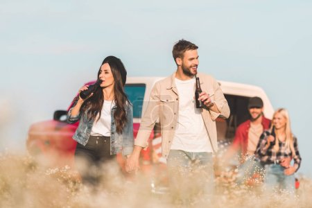 young happy couple drinking beer in flower field while their friends sitting in car trunk