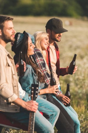 Photo for Group of young people drinking beer while sitting in car trunk in field - Royalty Free Image