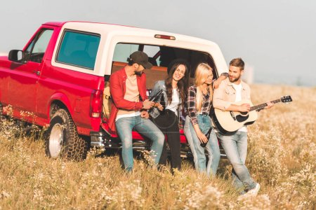 group of happy young people drinking beer and playing guitar while relaxing in car trunk in flower field