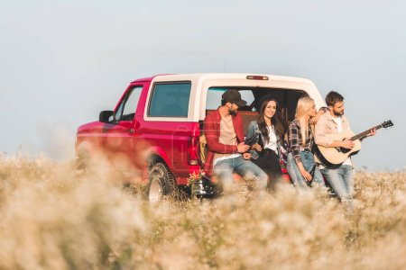 group of young friends drinking beer and playing guitar while sitting in car trunk in flower field