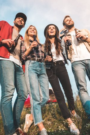 Photo for Bottom view of group of young people with beer bottles and guitar on field - Royalty Free Image