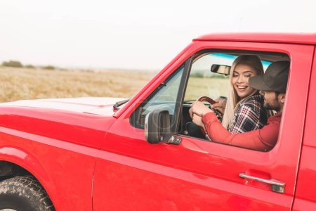 happy young couple sitting on drivers seat together and driving truck by field