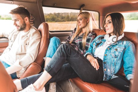 happy group of friends sitting in car while having trip