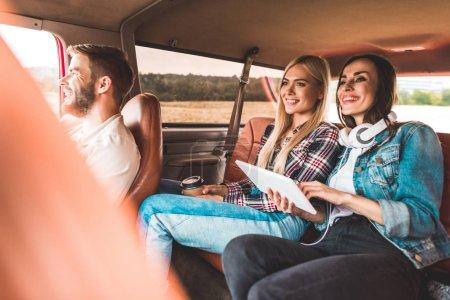 jeune groupe d'amis assis dans la voiture tout en ayant voyage