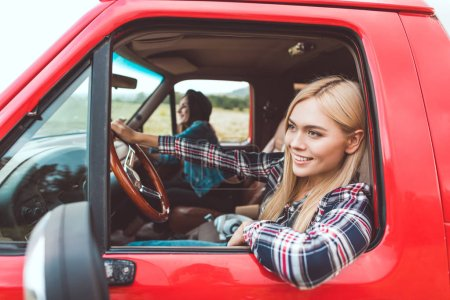 side view of happy young girlfriends having car trip and riding through fields