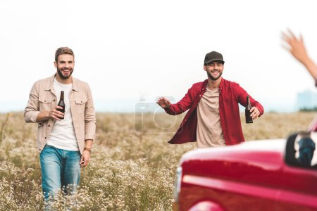 happy young men with beer running at car in field