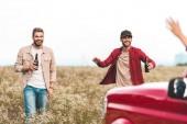 heureux jeunes hommes avec de la bière en voiture dans le champ