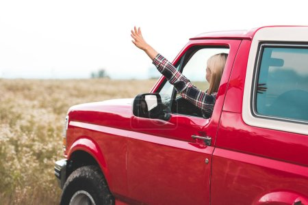 beautiful young woman driving car on flower field and waving