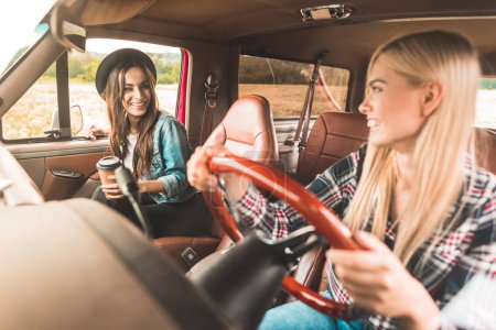 happy young girlfriends having car trip and chatting in car