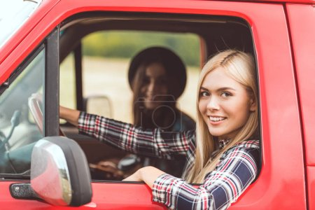 side view of smiling young girlfriends riding car and looking at camera