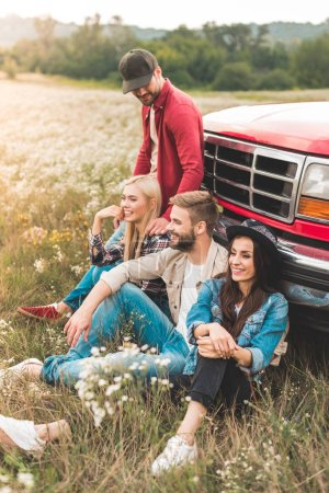 group of young car travellers sitting on flower field and leaning back on vintage truck