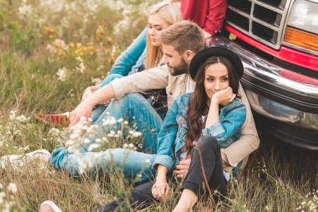 group of relaxed young car travellers sitting on flower field and leaning back on vintage truck