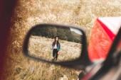 reflet de miroir de côté auto de belle jeune femme marchant dans le champ de la fleur seule